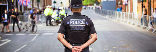 Male police officer standing in quiet street