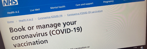 Blue background on computer screen of NHS Vaccine Booking System for Covid-19