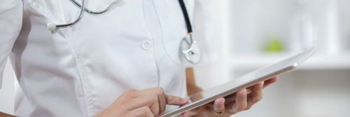 A doctor check their records on a tablet device