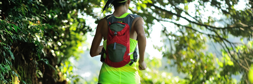 Female ultrarunner with a backpack in the forest