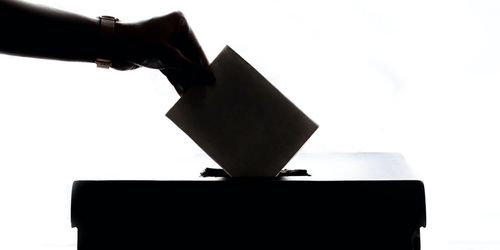 A picture of a hand putting a ballot in a box