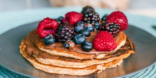 A picture of 3 pancakes with berries