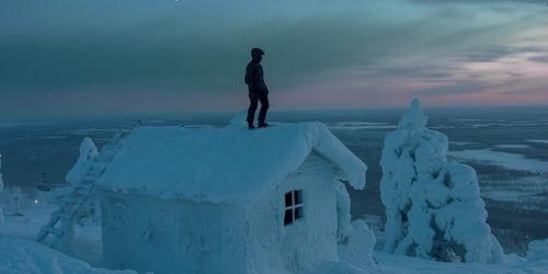 A man standing on a house covered in snow