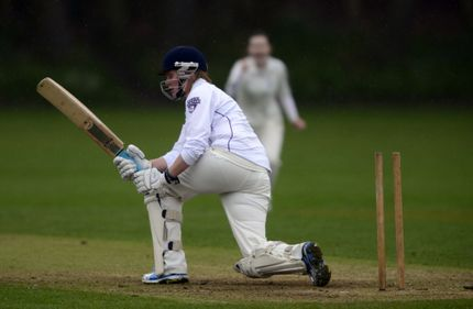 Female cricketer holding bat on one knee in front of wickets. One stump is missing