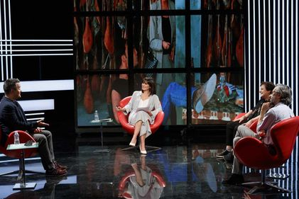 Four people sitting together talking on a TV set