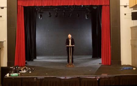 Professor Scholar standing on stage