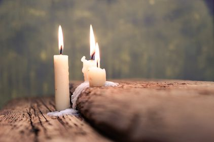 Candles burning on an old oak table
