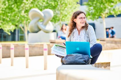 Student sat studying and smiling on campus