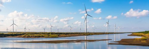 Wind turbines against a blue sky reflected in ground water