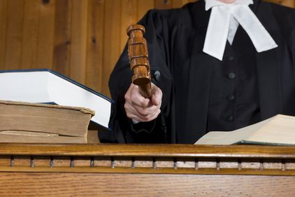 Judge In Traditional Court Robes Using the Gavel