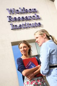 Two people stood outside the Wolfson Research Institute