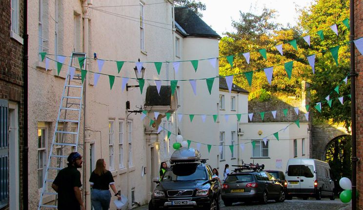 The street where Cuth's is situated on the Bailey. Bunting and cars visible as new students arrive.