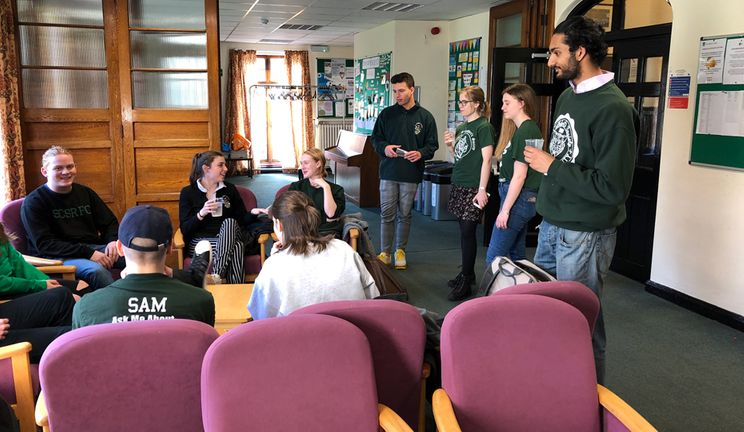 A group of students meeting in the Bailey Junior Common Room showing armchairs and posters.