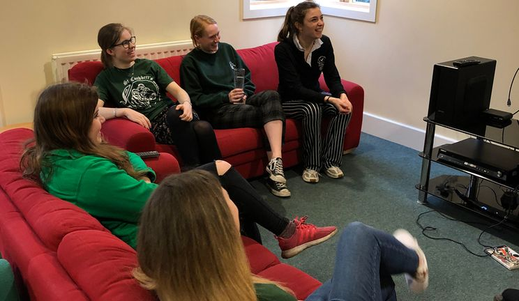 Students watching a flat-screen TV mounted on a wall, sitting on couches in the Junior Common Room at Parson's Field site.