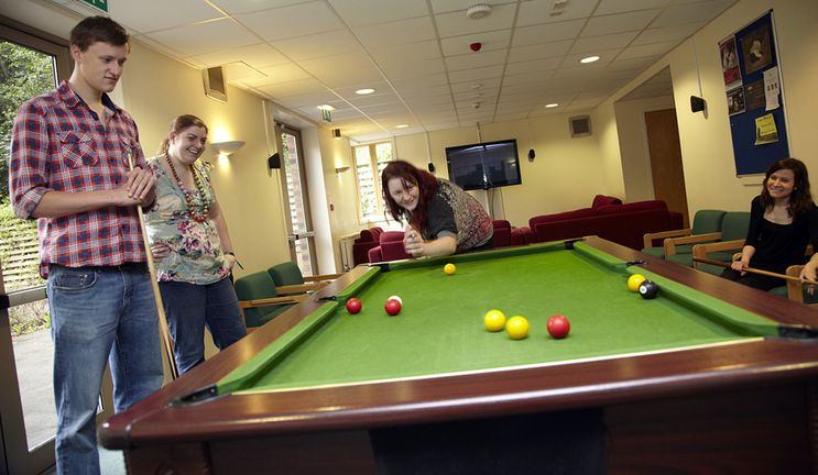 A mixed group of students playing pool in a modern common room.