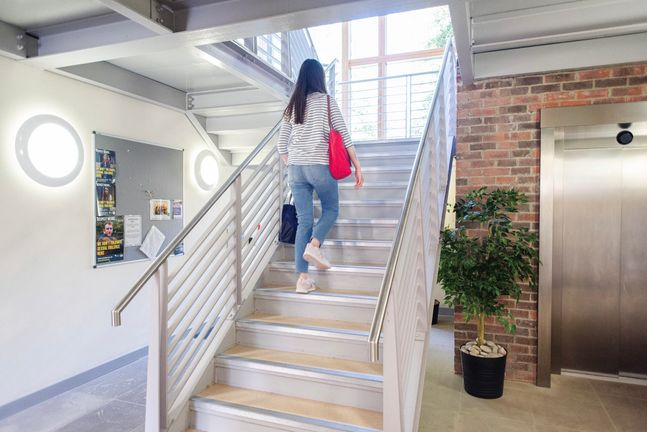 A student walking up the stairs in the Garth