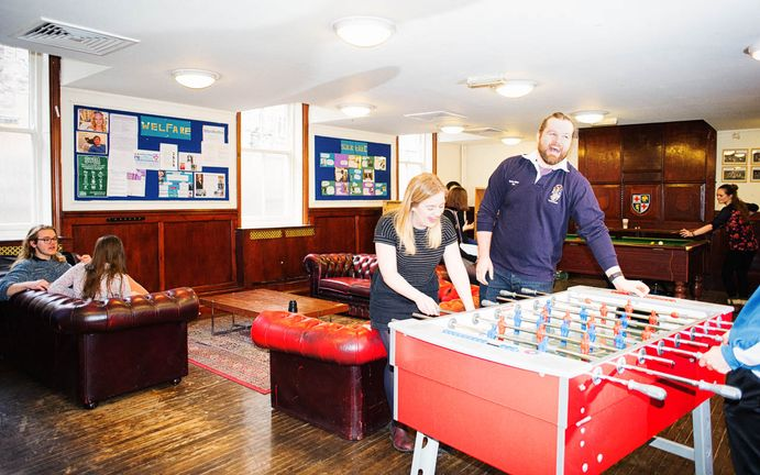 Students playing foosball, pool and sitting around chatting in a student common room