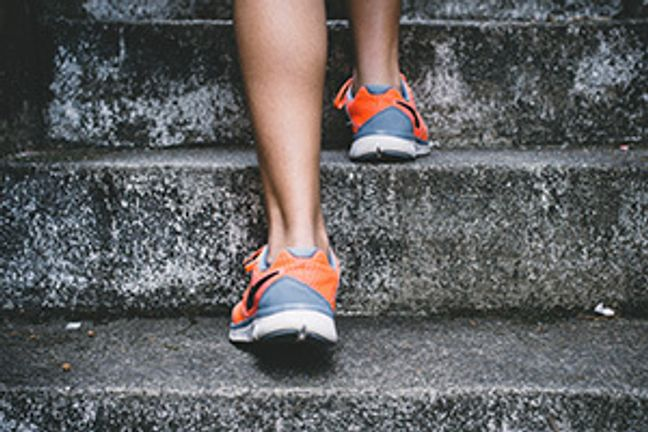 Person's feet in trainers running up steps