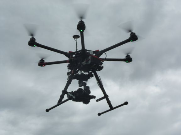 a UAV or drone with a camera attached flying in cloudy skies