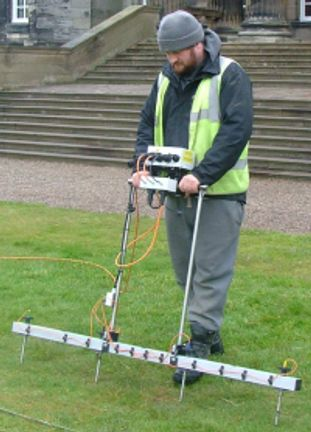 an archaeologist conducting an earth electrical resistance survey on the lawn of a stately home