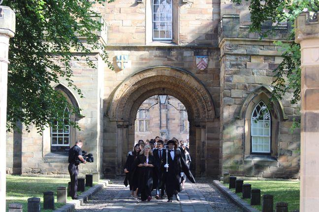 People walking through arch at graduation