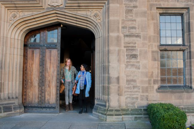 Two students exiting a historic building.