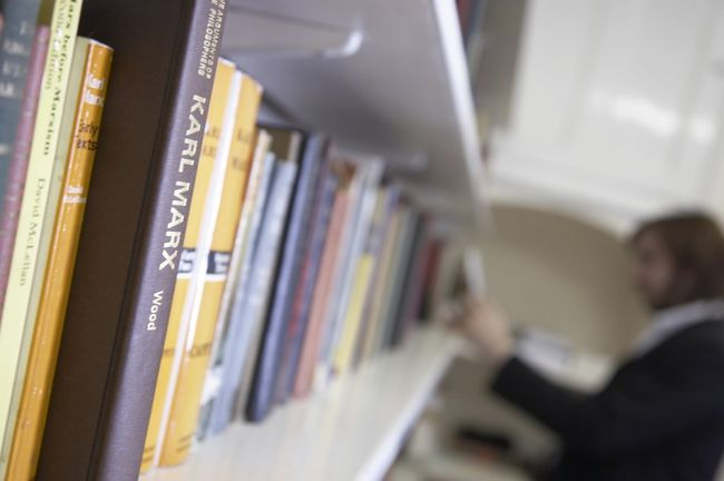 A shelf of books in a library with a student browsing
