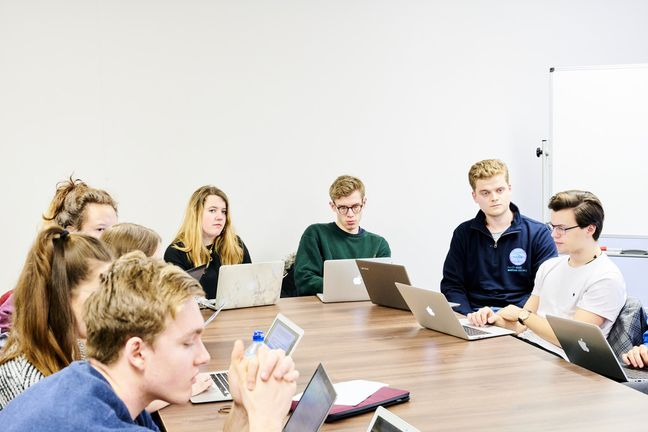 A group of students discussing work around a table
