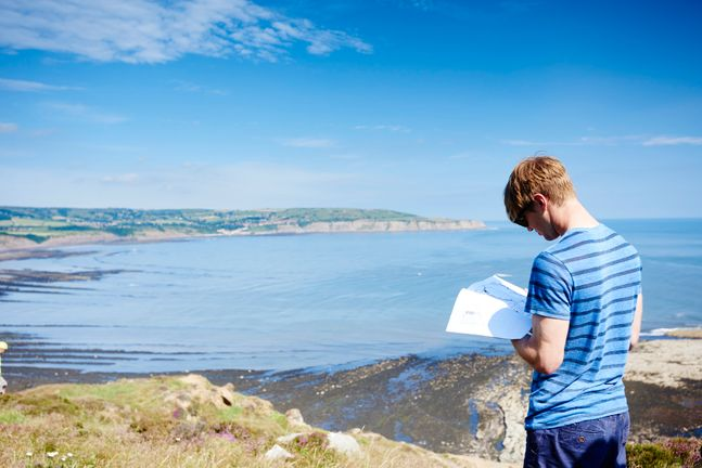 Man reading while overlooking sea
