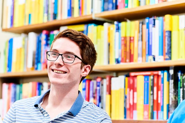 Student in front of a bookshelf, smiling a the camera.