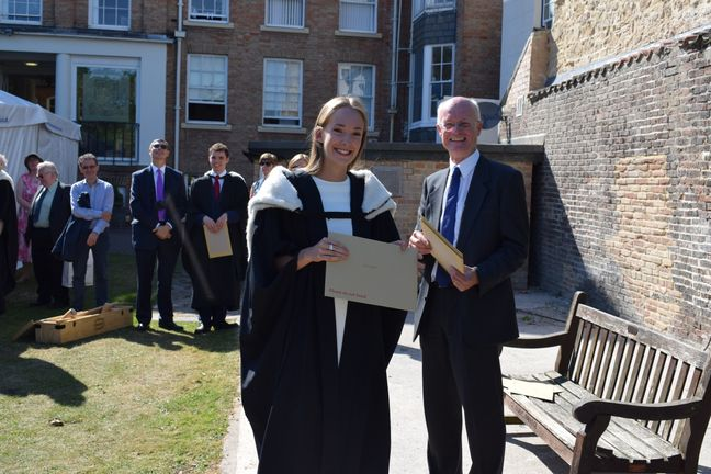 Student receiving their degree, wearing graduation robes