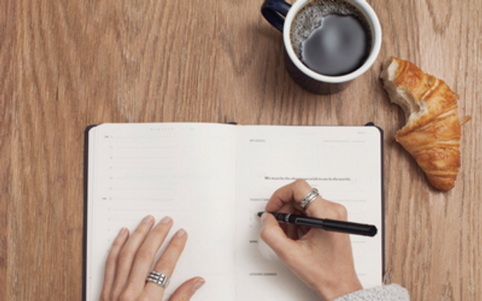 A person writing in a notebook with a cup of coffee