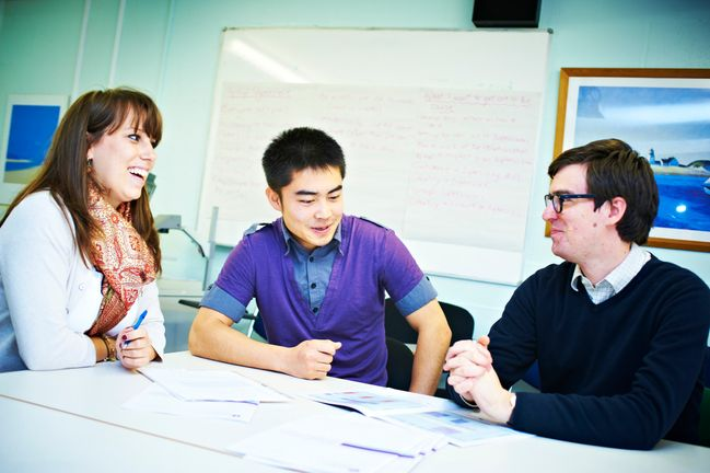 Students sat round a table laughing with their tutor