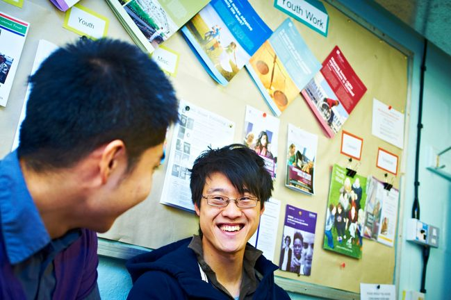 A student smiling in conversation with another classmate