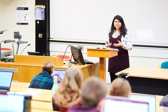 Someone at a lectern giving a lecture to a group of students