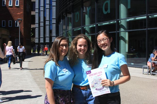 Three students posing and holding an open day brochure