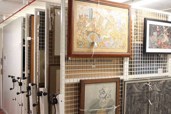 paintings hanging on a series of vertical mesh racks with other cupboards visible behind