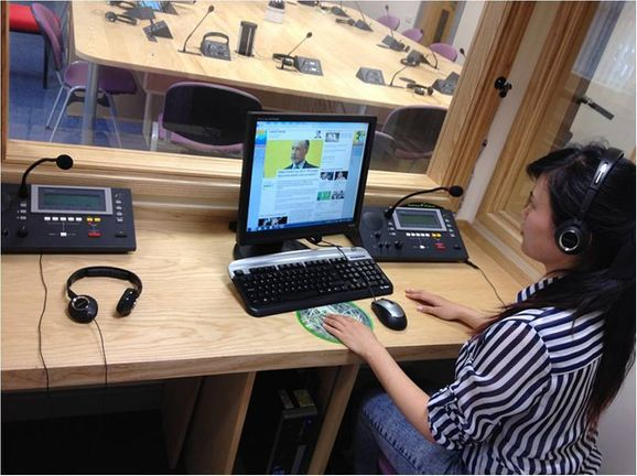 A student working on a computer in an interpreting booth