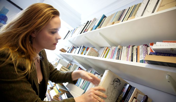 A person putting a book back on a bookshelf