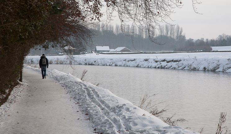 The River Wear in Winter with snow on the bank side and a lone person walking