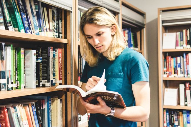 Student in library looking at book