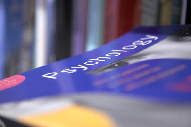 A Psychology textbook on a library shelf.
