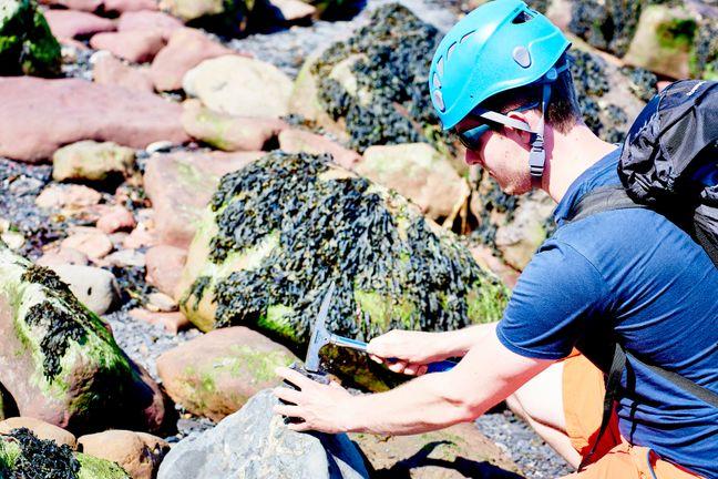 Student in hardhat using hammer to break rock at Ravenscar beach