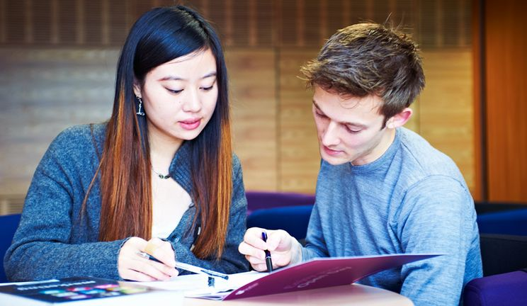 Two students working together over open academic textbooks