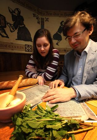People look at medieval recipes with food on the table