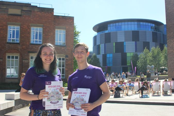 Two Durham students on campus with open day brochures