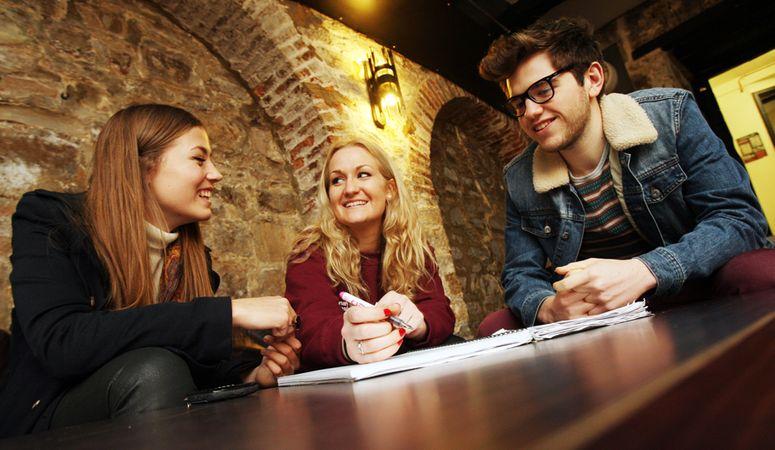 Three undergraduates gather around a table to study