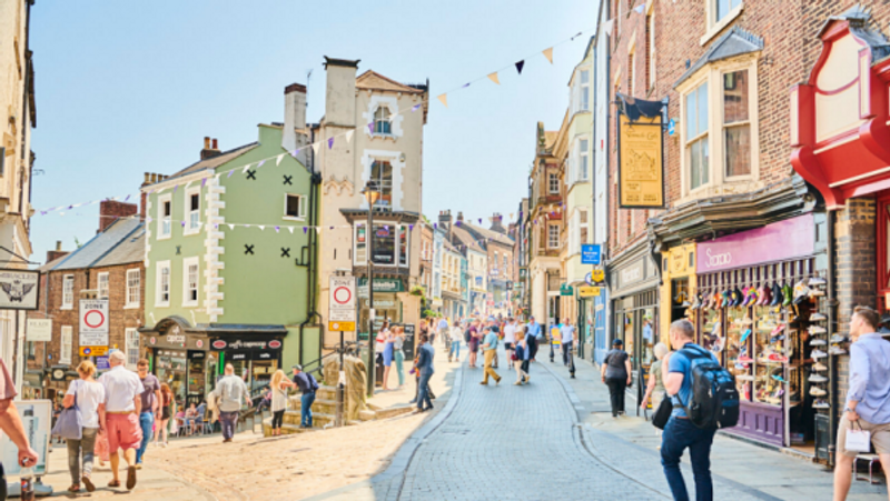 A street in Durham, with old buildings and people walking down the street