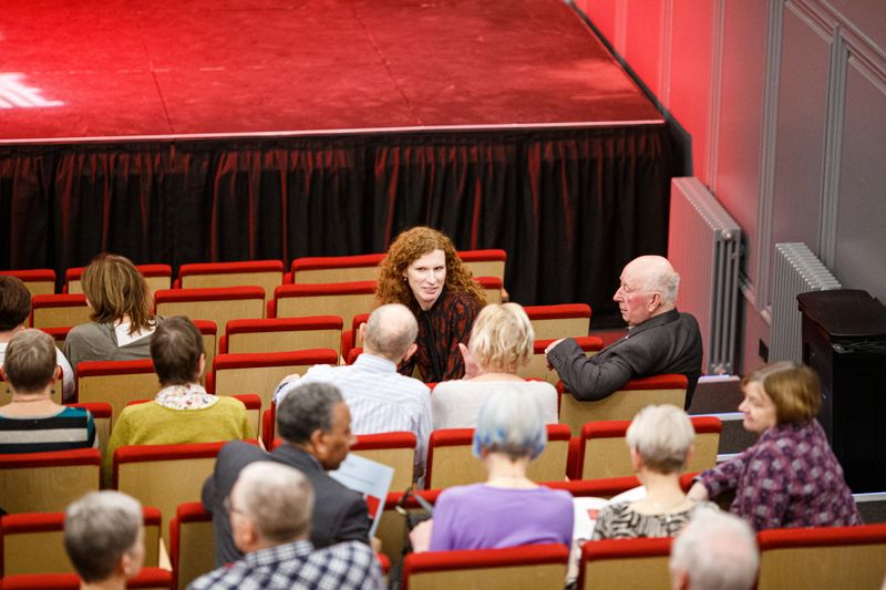 Audience members chatting in their seats at the theatre