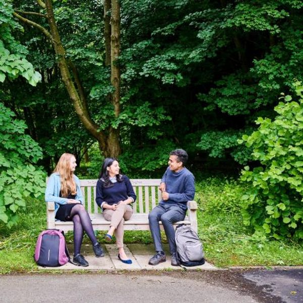 Students sitting on an outdoor bench in the gardens